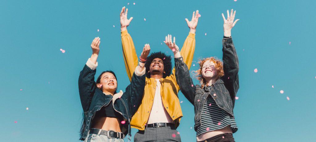 Jeunes souriant qui lancent des pétales