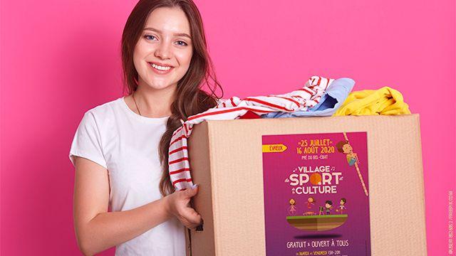 femme portant un carton rempli de vêtements