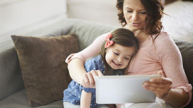 Maman qui regarde un film sur une tablette avec sa fille