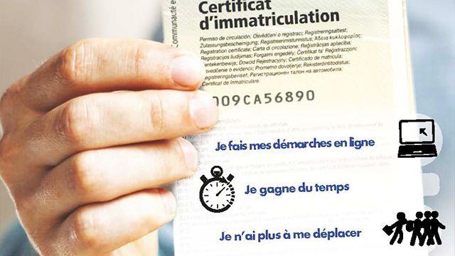 lien pour les démarches en ligne et en fond une certificat d'immatriculation tenu dans une main