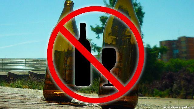 symbole alcool interdit sur fond de bouteilles dans une rue