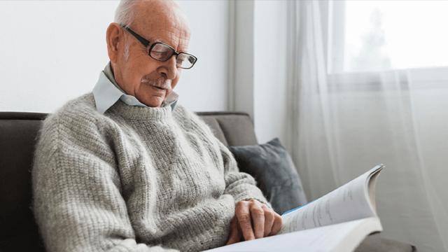 homme âgé qui lit sur le canapé