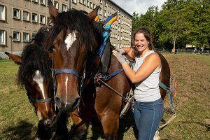 Eleveuse souriante à côté du cheval